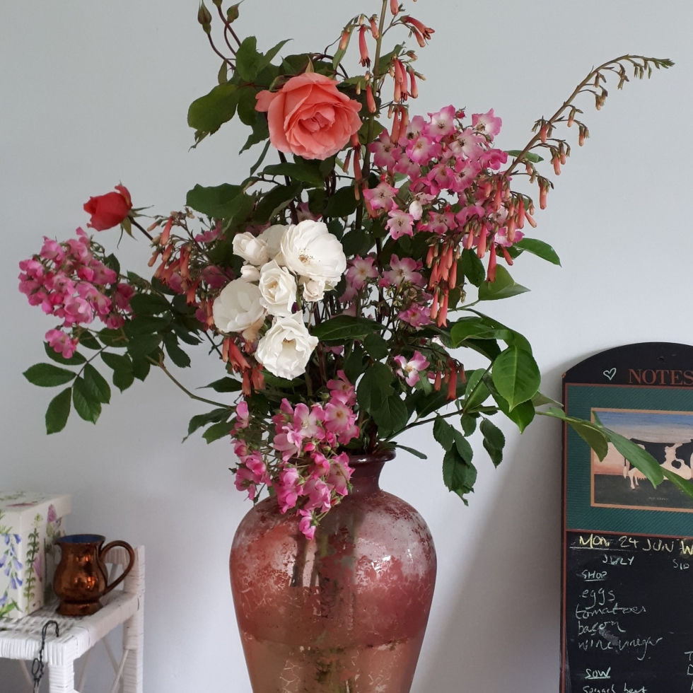 Roses, penstemon, and laurel in a big red vase