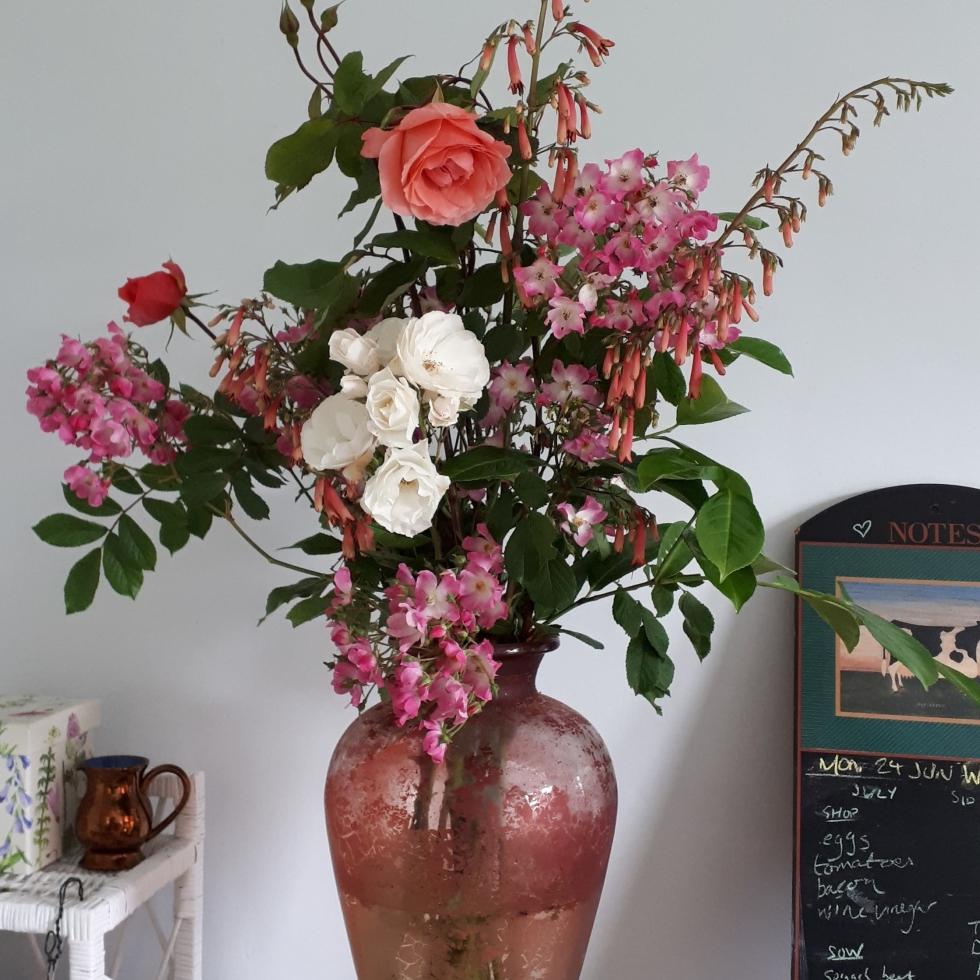 Roses, penstemon, and laurel in a big red vase